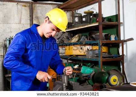 blue collar factory worker working in workshop - stock photo