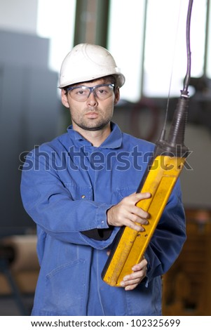 Blue collar worker using a crane in factory - stock photo