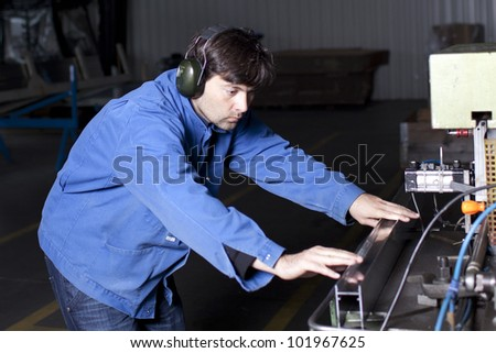 Blue-collar worker working in fabric - stock photo