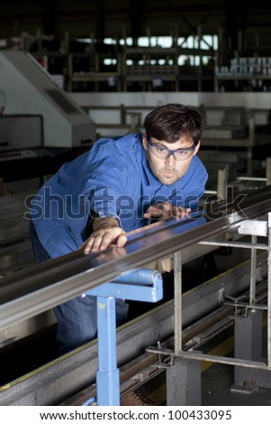 Blue-collar worker working in fabric checking aluminum - stock photo