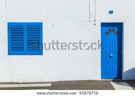 Blue colonial window and door on a wall made out of wood