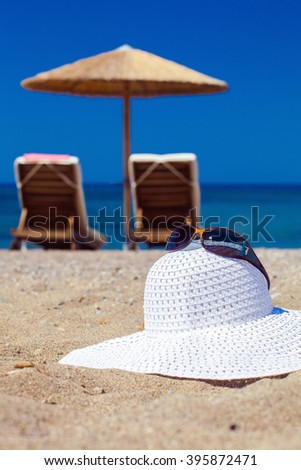 blue color of sea and hat on sand. Focus on hat - stock photo