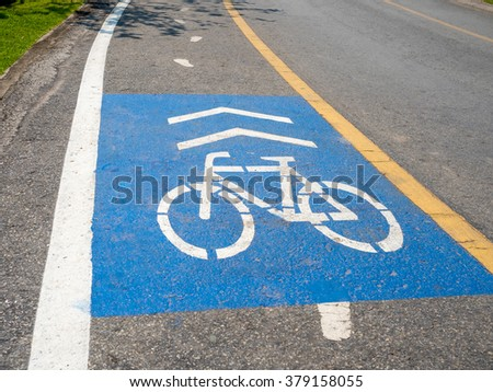 blue color painted on asphalt road indicating that the lane for bicycle