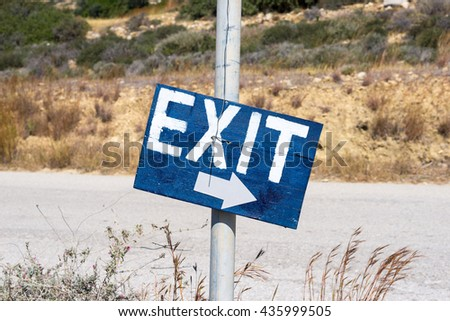 Blue colored Exit street sign in the middle of nowhere seen in south-central Crete. On the way to Matala, sign with arrow shows the way to walk or to drive - stock photo