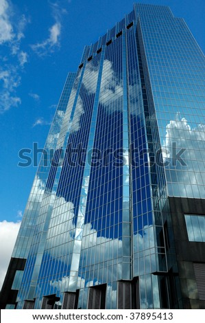 Blue Colored  Glass Skyscraper Reflecting Clouds - stock photo