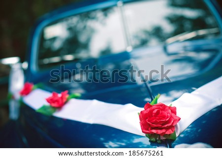 Blue colored vintage wedding car decorated with roses and white ribbon. Hipster style. Daylight. Close up. Copy-space. Outdoor shot - stock photo