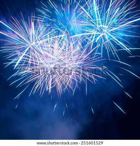 Blue colorful fireworks on the black sky background. Holiday celebration. - stock photo