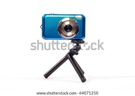 blue compact camera on mini Tripod - stock photo