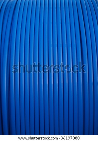 Blue conduit pipe on a large spool - stock photo
