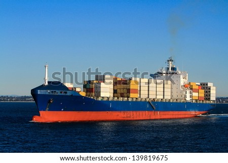 Blue container cargo ship at sea.