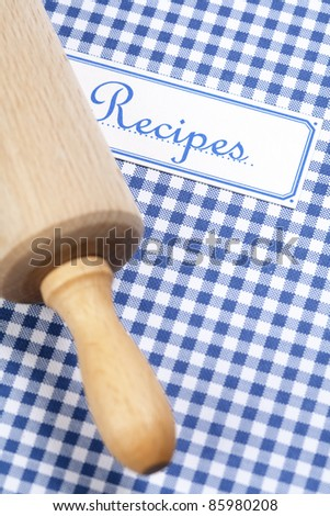 Blue cookbook and rolling pin - stock photo