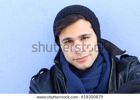 Blue copyspace portrait of a young man in black leather jacket freezing in the ice cold winter snow - stock photo