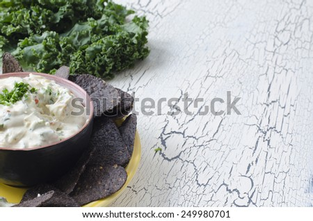 blue corn tortilla chips with ranch vegetable dip kale and copy space - stock photo