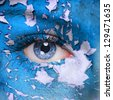 Blue cracked paint on woman face - stock photo