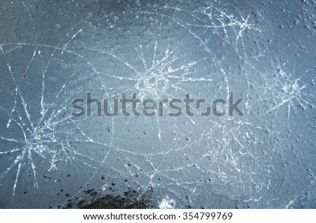 Blue cracked thin ice on a puddle, cold winter background - stock photo