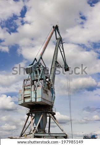 Blue crane in the river harbor with dynamic clouds and blue sky in background - stock photo