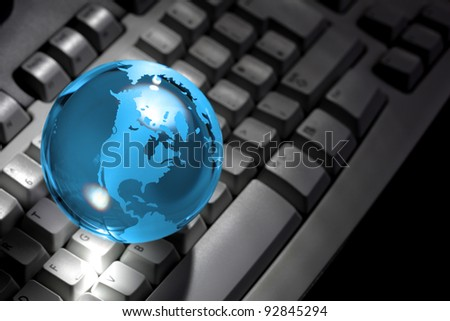 Blue crystal earth globe resting on a computer keyboard - stock photo