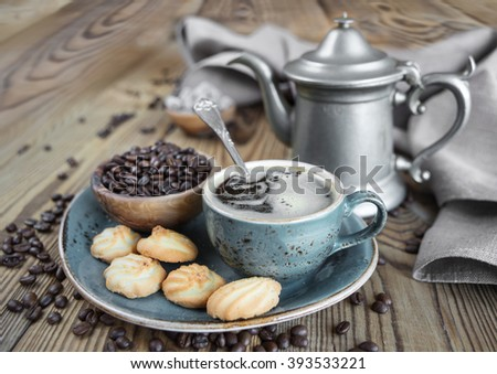Blue cup of black coffee, biscuits and coffee pot  surrounded by linen cloth, sugar pieces and coffee beans on old wooden table - stock photo