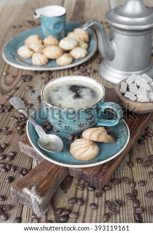 Blue cup of black coffee, biscuits, creamer, coffee pot,  sugar pieces and coffee beans on old wooden table - stock photo