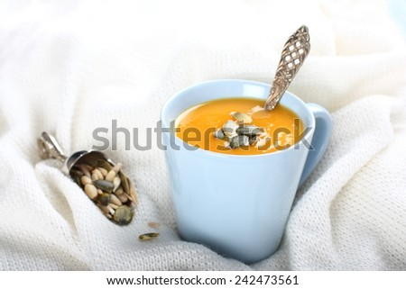 Blue cup of pumpkin soup on the knitted woolen fabric - stock photo