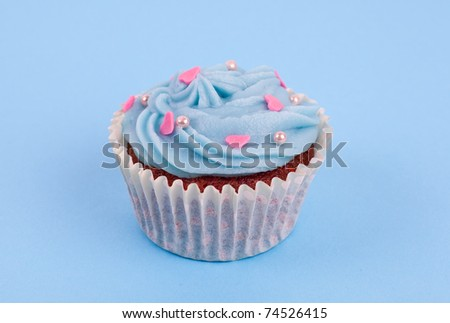 Blue cupcake birthday surprise with pink hearts and pearls - stock photo