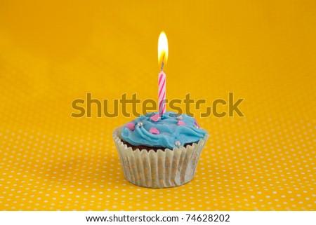 Blue cupcake on yellow background - stock photo
