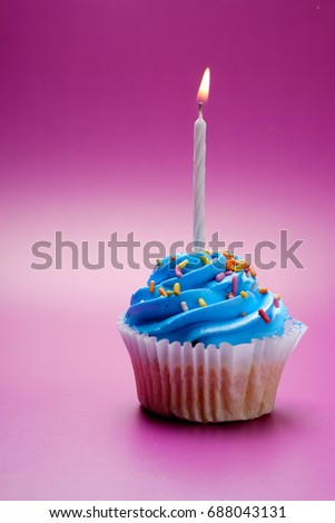 Blue cupcake with candle on color background