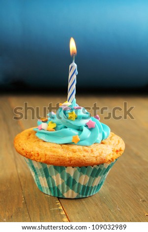 Blue cupcake with candles on a blue background - stock photo