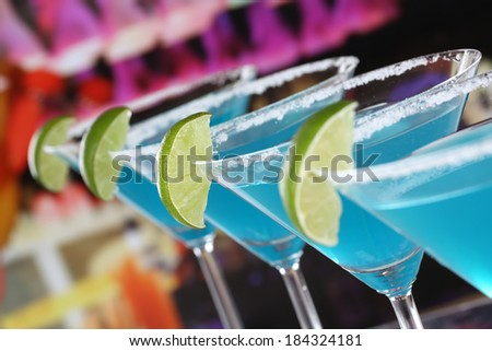 Blue Curacao Cocktails in Martini glasses in a bar or a party - stock photo