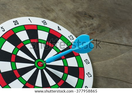 Blue darts arrows in the target center on wooden background. Success hitting target aim goal achievement concept background. close up. - stock photo
