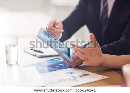 Blue data against business people using tablet - stock photo