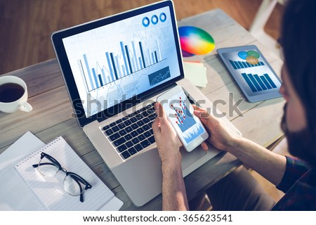 Blue data against high angle view of editor using smartphone and laptop - stock photo