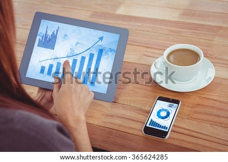 Blue data against over shoulder view of hipster woman using tablet - stock photo