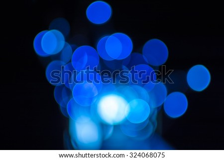 Blue defocused bokeh Christmas lights on a wooden support - stock photo
