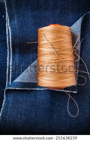 Blue Denim Jean Fabric with Threads Reel and Needle for Embroidery / Concept and Idea of Denim Industry, Sewing and Fashion, Vintage Rustic Style. Pattern, Background, Wallpaper and Textured. - stock photo