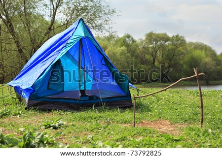 Blue deployed tent stands on river bank in green forest on summer day - stock photo
