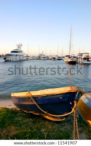 Blue dinghy at sunset with marina yachts in the background. - stock photo