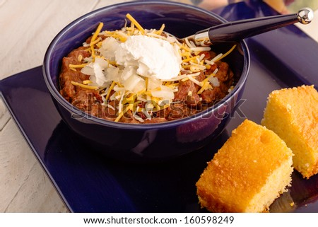 Blue dinner plate with bowl of elk meat chili with onions, sour cream and shredded cheese - stock photo