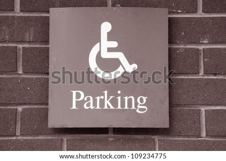 Blue Disabled Parking Sign against Brick Wall Background