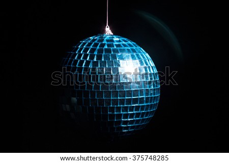 Blue disco ball in shadow on black background