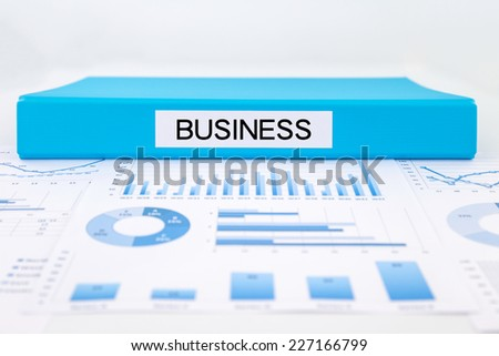 Blue document binder with business word place on graphs and charts of strategic plan
