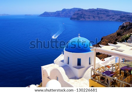 Blue dome church with boat, Oia village, Greece - stock photo