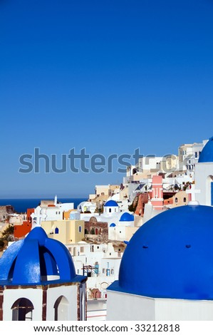 blue dome churches and classic cyclades architecture over the mediterranean sea in oia santorini the famous greek island - stock photo