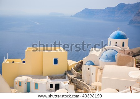 Blue domed church in Oia overlooks the spectacular caldera surrounding beautiful island of Santorini, Greece - stock photo