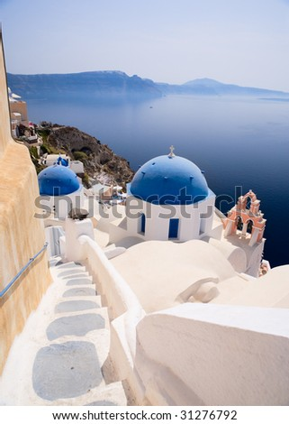 Blue domed church in Oia overlooks the spectacular caldera surrounding the beautiful island of Santorini, Greece
