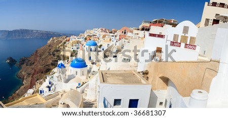 Blue domed church in Oia overlooks the spectacular caldera surrounding the beautiful island of Santorini, Greece - stock photo