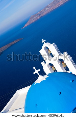 Blue domed church overlooks the spectacular caldera surrounding beautiful island of Santorini, Greece - stock photo