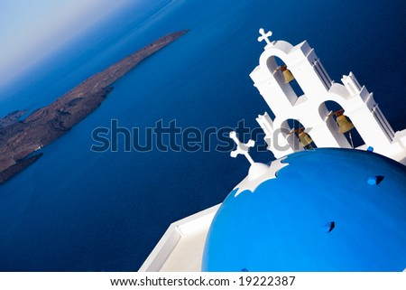 Blue domed church overlooks the spectacular caldera surrounding the beautiful island of Santorini, Greece - stock photo