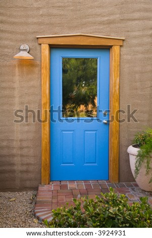 Blue door and Stucco wall with flower pot an brick porch - stock photo