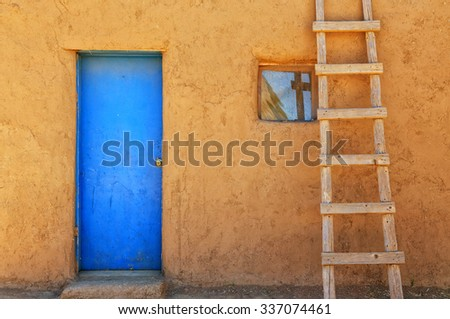 Blue door and wooden ladder at Taos Pueblo in northern New Mexico. - stock photo